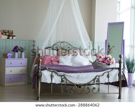 Classic interior light bedroom with large bed and chest of drawers. - stock photo