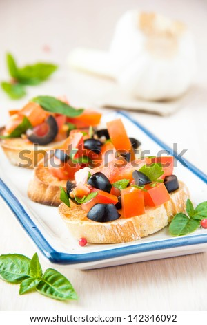 Classic Italian appetizer bruschetta with tomato, basil and black olives on plate