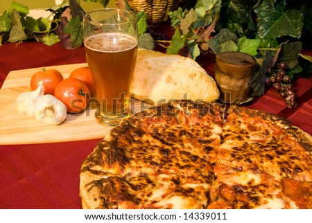 Classic Italian food setting with wine, pizza, bread and trimmings. - stock photo