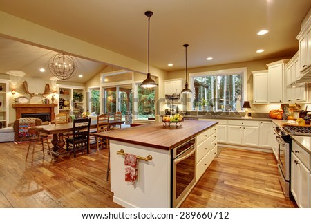 Classic kitchen with hardwood floor, an island, and connected dinning room. - stock photo