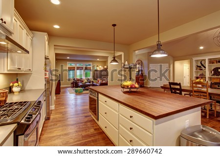 Classic kitchen with hardwood floor, an island, and connected dinning room and living room. - stock photo