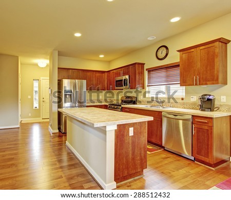 Classic kitchen with hardwood floor, island, and window.