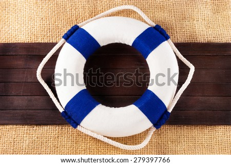 Classic lifebuoy on a wooden planks over sackcloth background. - stock photo