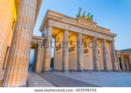 Classic low angle view of famous Brandenburger Tor (Brandenburg Gate), one of the best-known landmarks and national symbols of Germany, in twilight during blue hour at dawn, Berlin, Germany - stock photo