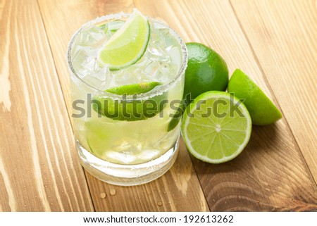 Classic margarita cocktail with salty rim on wooden table with limes - stock photo
