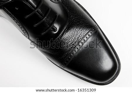 Classic men's black shoe - macro on white background - stock photo