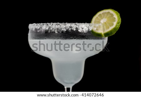 Classic Mexican Cocktail - Margarita in glass with cocktail tubes. Ingredients of cocktail - lime juice, ice, tequila, salt and orange liqueur. Isolated on black bacgkround.  - stock photo