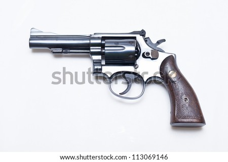 Classic .38mm revolver handgun with bullets on white background. - stock photo