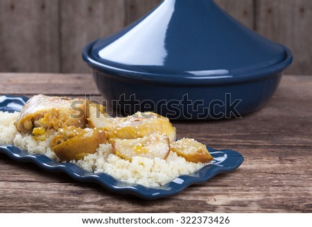 Classic Moroccan chicken tagine with caramelized pears and sesame on the wooden table in rustic style. Selective focus. - stock photo
