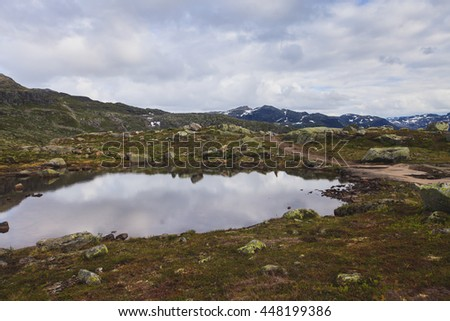 Classic norwegian scandinavian summer mountain landscape view with mountains, fjord, lake with a blue sky, Norway