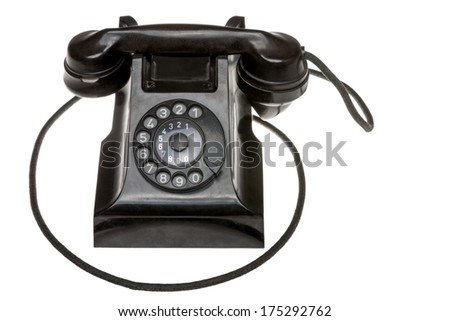 Classic old black rotary dial-up telephone instrument, closeup frontal view with the handset in place over a white studio background - stock photo
