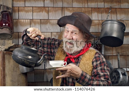Classic Old West style cowboy cook with felt hat, grey whiskers, red bandana. He is ready to pour tea into a white china tea cup. - stock photo
