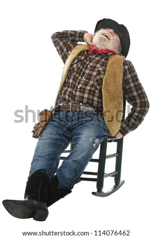 Classic Old West style laughing cowboy with felt hat, grey whiskers, revolver. He stretches leaning back in rocking chair. Isolated on white, vertical, copy space. - stock photo