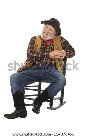Classic Old West style smiling cowboy with felt hat, grey whiskers, revolver. He relaxes in a rocking chair. Isolated on white, vertical, copy space. - stock photo