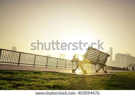 Classic park bench from below angle against morning sun. A beautiful winter morning at the park. - stock photo
