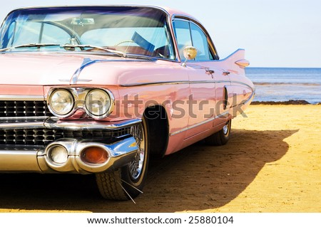 Classic pink car at beach - stock photo