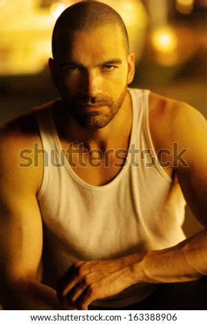 Classic portrait of a sexy moody man in golden light and shadow - stock photo