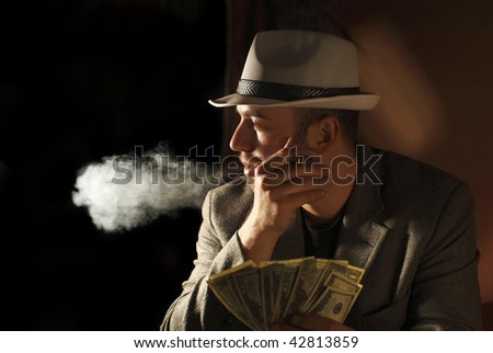 classic portrait of young gangster smoking and count dollars - stock photo