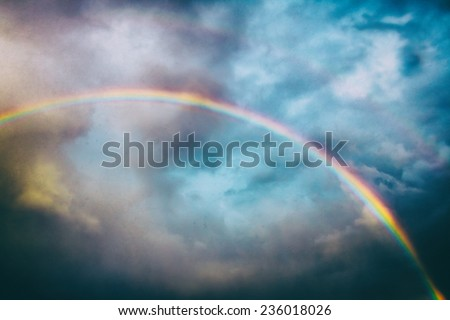 Classic Rainbow. A rainbow across the sky, edited with vintage film effects. - stock photo