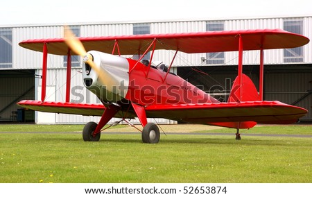 Classic red biplane ready for a flight - stock photo