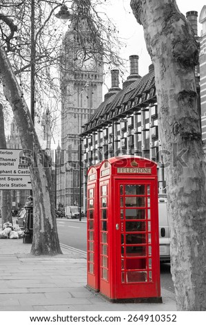 Classic red British telephone boxes with Big Bang in the background. Black and with image with selective red color correction. - stock photo
