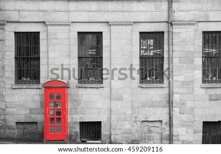 classic red telephone booth against white and black old building wall at the Rock, Sydney
