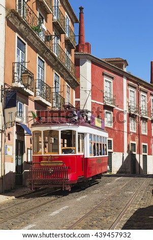 Classic red tram bus in Alfama district of Lisbon, Portugal - stock photo