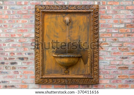 classic retro water feature installation against a face-brick wall - stock photo