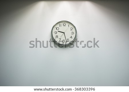 Classic round wall clock on the grey background. - stock photo