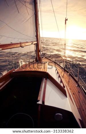 Classic sailing yacht sails towards the setting sun - stock photo