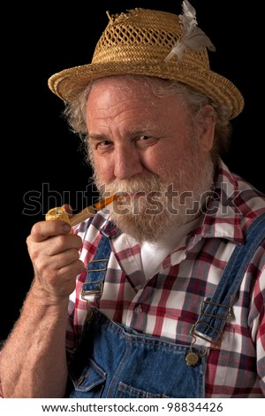 Classic smiling senior farmer with straw hat, plaid shirt, bib overalls, and corn cob pipe. Vertical layout, isolated on black background with copy space. - stock photo