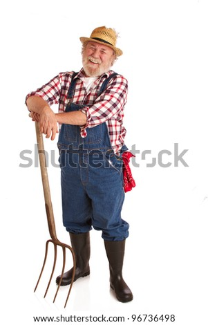 Classic smiling senior farmer with straw hat, plaid shirt, bib overalls, leaning on hay fork. Vertical layout, isolated on white background with copy space.