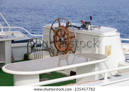 classic steering wheel on yacht - stock photo
