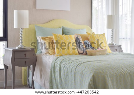 Classic style bedside table with reading lamp next to cozy style bedding with many style of green and yellow pillows - stock photo