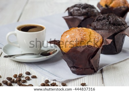 Classic style espresso shot with chip muffin and coffee beans on white wooden table. - stock photo