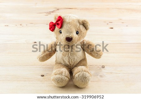 Classic teddy bear red bow toy on wood background.