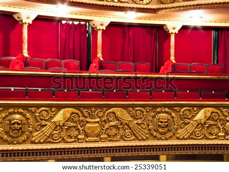 classic theater balcony with red chairs and golden details - stock photo