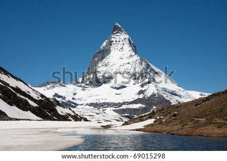 Classic view on the Matterhorn with the partly frozen Riffelsee in the foreground. - stock photo