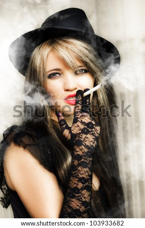 Classic vintage portrait of sixties female film actress smoking cigarette on set in a movie and cinema concept - stock photo