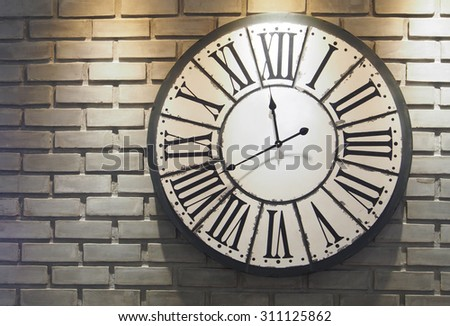 Classic wall clock on brick wall. - stock photo