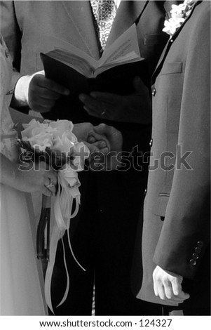 Classic wedding in black & white.  Note hesitance of groom, not holding bride's hands. - stock photo