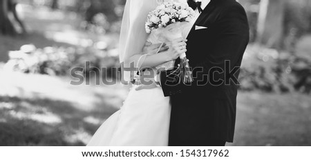 classic wedding picture, Married Couple embracing outside, black and white - stock photo