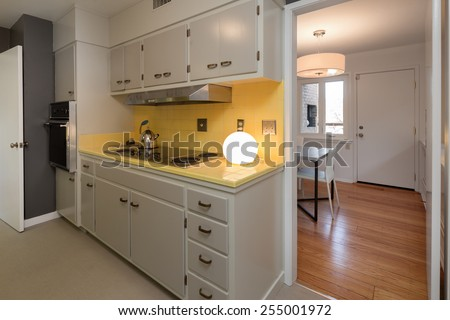 Classic white yellow kitchen with retro art deco light and adjacent dining area.  - stock photo