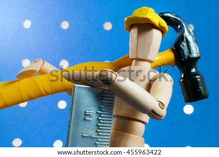 Classic wooden dummy as a builder on a blue background.