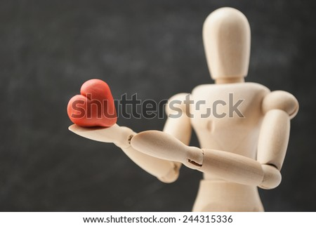 Classic wooden dummy holds red little heart for Valentine's Day. - stock photo