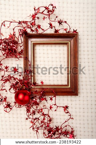 Classic wooden frame decorated with Christmas foil stars and red  ball on wool plaid background   - stock photo
