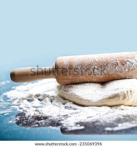 Classic wooden rolling pin with freshly prepared dough and dusting of flour on black background - stock photo