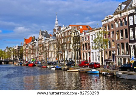 Classical Amsterdam view. Boat floats on the channel on the background of Dutch houses. Urban scene. - stock photo
