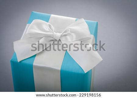 classical blue giftbox with white ribbon on gray background