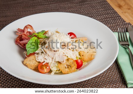 Classical Caesar salad with  sliced chiken meat, grilled bacon, lettuce leaves, crackers and cherry tomatoes decorated with basil and parmesan  served in white round  plate - stock photo